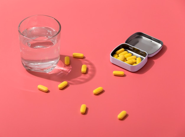 High angle of pills in metal container with glass of water