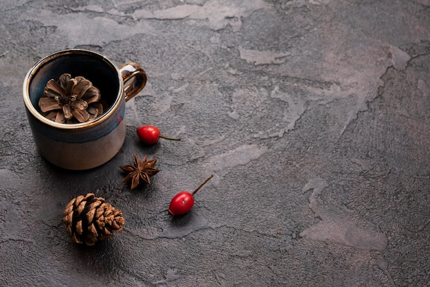 High angle of pine cone in cup with rosehip and anise