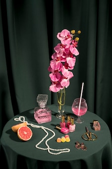 High angle pink orchid next to fashion items