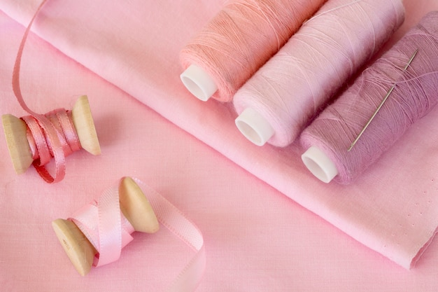 High angle of pink thread rolls with ribbon and textile