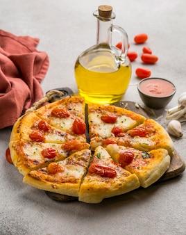 Angolo alto di pizza tagliata a fette con olio e pomodori