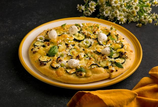 Alto angolo di pizza sulla piastra con fiori