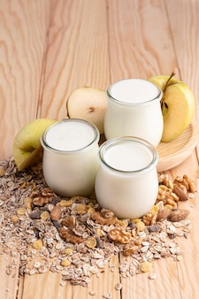 High angle plain yogurt in jars with oats and apple