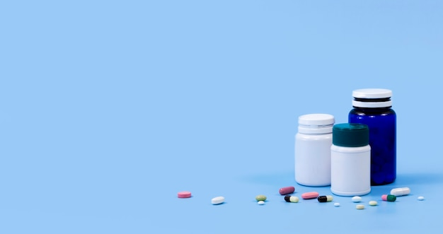 High angle of plastic containers with pills and copy space