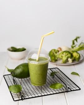 Пластиковый стаканчик под большим углом с зеленым смузи