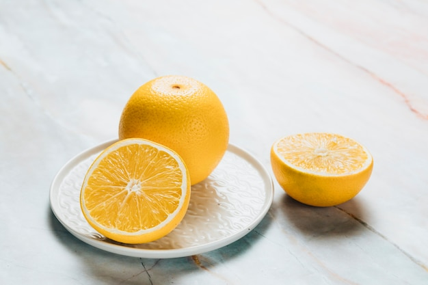 High angle of plate with lemon on marble background