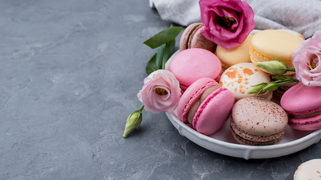 High angle of plate with roses and macarons