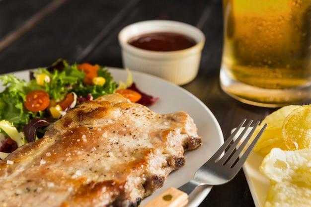 Angolo alto del piatto con bistecca e birra