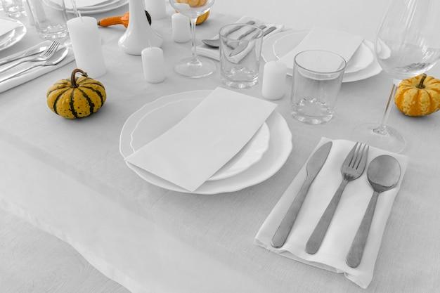 Alto angolo di piatti e carino sul tavolo bianco