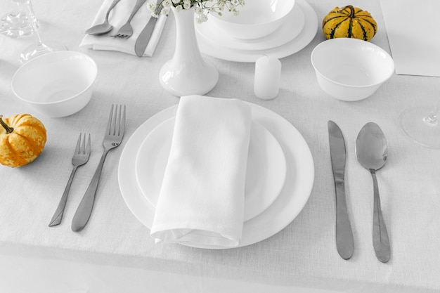 High angle of plates and cuterly on white table