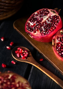 High angle of pomegranate fruit with wooden spoon