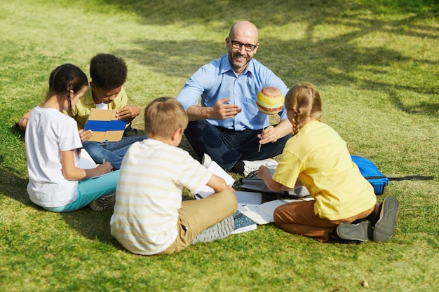 High angle portrait of bald male teacher pointing at planet model and smiling while talking to group of children during outdoor class in sunlight, copy space