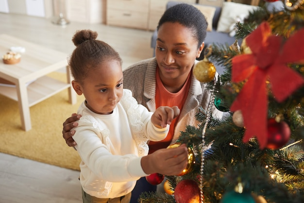 High angle portrait of cute african-american girl decorating christmas tree with smiling happy mom in cozy home interior