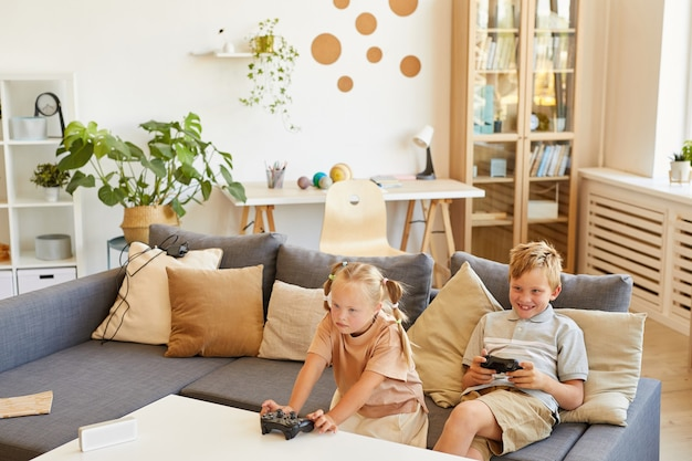 High angle portrait of cute girl with down syndrome playing video games with brother while sitting on couch in living room, copy space