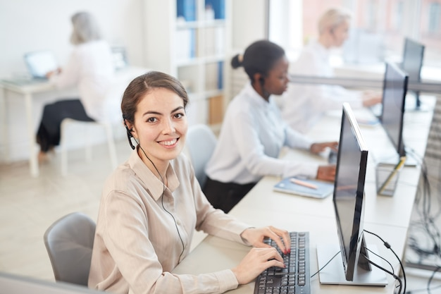 High angle portrait of female operator wearing headset and smiling while sitting in row at call center