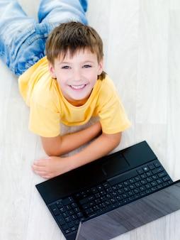 Ritratto di alto angolo di ragazzino allegro felice con il computer portatile sul pavimento