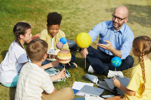 High angle portrait of male teacher pointing at planet model and smiling while enjoying outdoor astronomy class with group of children, copy space