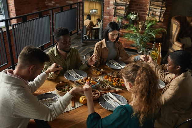 High angle portrait of multi-ethnic group of elegant young people praying and holding hands while sitting at dinner table during thanksgiving celebration,