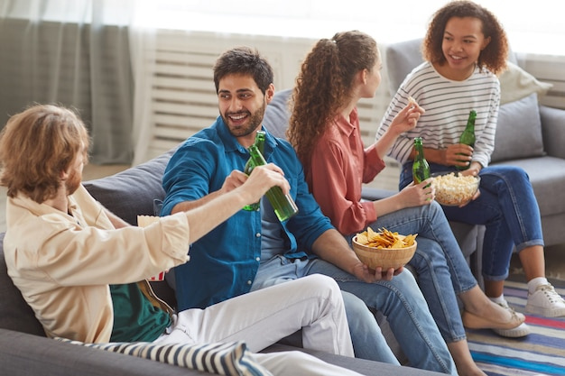 High angle portrait of multi-ethnic group of friends clinking beer bottles while watching tv together sitting on comfortable sofa at home