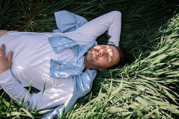 들판의 풀밭에서 휴식을 취하는 40세 남자의 높은 각도 초상화. 자연과 하나되는 소규모 비즈니스 개념