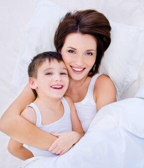 ベッドに横たわって笑っている若い母親と彼女のかわいい息子の高角度の肖像画