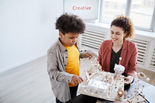 アートとクラフトのレッスン中に女性教師に学校のプロジェクトを提示するアフリカ系アメリカ人の少年の高角度の肖像画