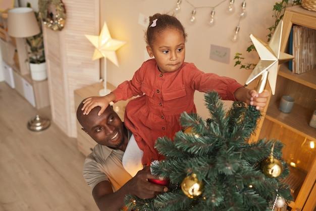 家でホリデーシーズンを楽しみながら父親が彼女を助けてクリスマスツリーに星を置くアフリカ系アメリカ人の女の子の高角度の肖像画