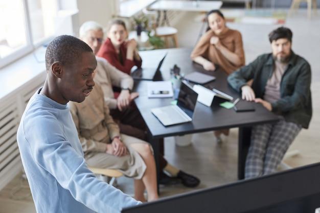 Высокий угол портрета афроамериканца, который делает презентацию в офисе для разнообразной бизнес-команды и указывает на цифровой экран, копирует пространство