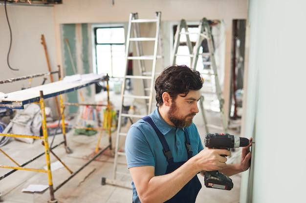 一人で家を改築しながら壁を掘削するひげを生やした建設労働者の高角度の肖像画、コピースペース