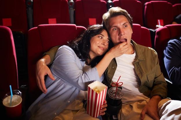 Портрет беззаботной молодой пары под высоким углом, смотрящей фильм в кинотеатре и едящей попкорн, копировальное пространство
