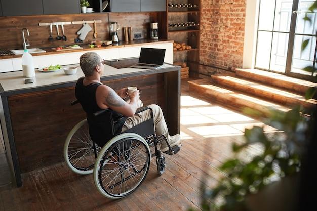 自宅でラップトップを介してビデオを見ている障害を持つ現代の入れ墨の女性のハイアングルの肖像画、コピースペース