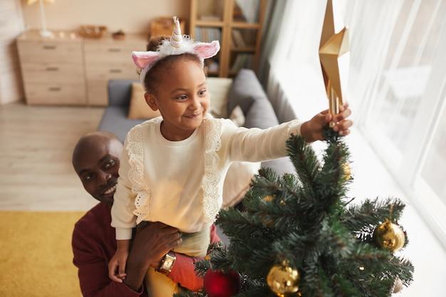 家でホリデーシーズンを楽しみながら彼女を助けて愛する父と一緒にクリスマスツリーに星を置くかわいいアフリカ系アメリカ人の女の子の高角度の肖像画