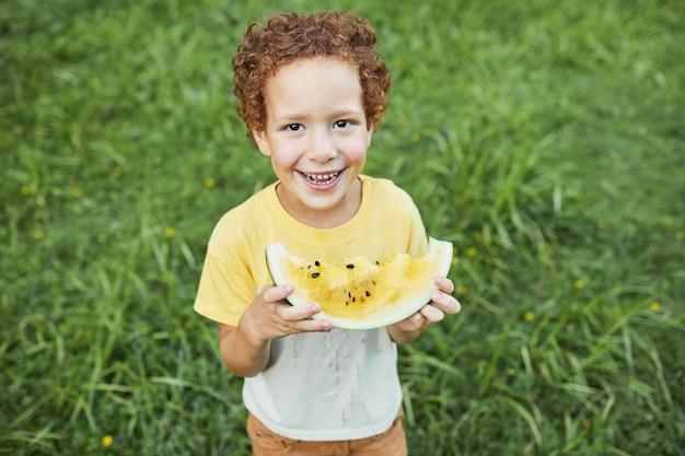 屋外でスイカを保持し、カメラのコピースペースで笑っているかわいい巻き毛の少年のハイアングルの肖像画