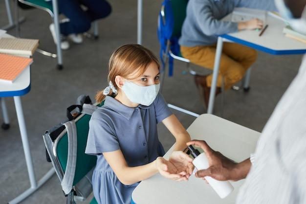 학교 교실에서 손을 소독하는 귀여운 소녀의 높은 각도 초상화, 코비드 안전 조치, 복사 공간
