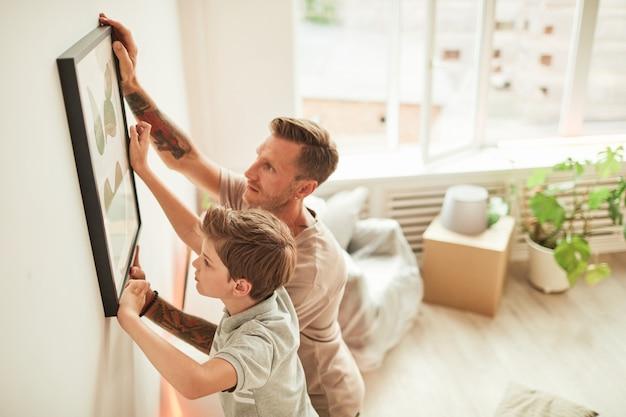 Портрет отца и сына под высоким углом, висящие на стене картины во время переезда в новое домашнее пространство