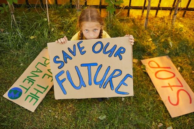 Save our futureの看板を持って、屋外の芝生に座って自然に抗議しながらカメラを見上げるそばかすのある女の子のハイアングルの肖像画、コピースペース