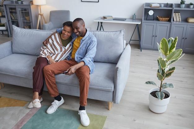 自宅のソファに座って、一緒にテレビや映画を見ている幸せなアフリカ系アメリカ人のカップルのハイアングルの肖像画、コピースペース