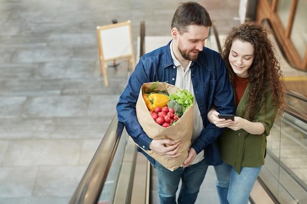 Портрет под высоким углом счастливой современной пары, держащей сумку с продуктами, поднимаясь по эскалатору в торговом центре