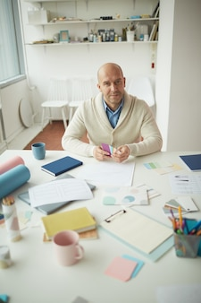 웃 고 직장에서 포즈를 취하는 동안 색상 견본을 들고 성숙한 남성 디자이너의 높은 각도 초상화, 복사 공간