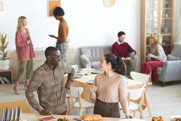 屋内でディナーパーティーのために料理をしながらお互いを見て、笑顔の混血の大人のカップルのハイアングルの肖像画、