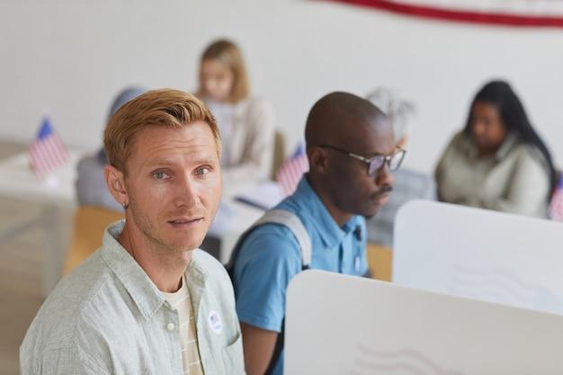 選挙日に投票ブースに立っている間、現代の金髪男性のハイアングルの肖像画、コピースペース