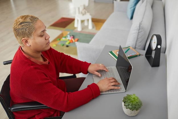 Высокий угол портрета современной женщины смешанной расы, использующей инвалидное кресло, во время работы из дома за столом с детскими игрушками в фоновом режиме, копией пространства