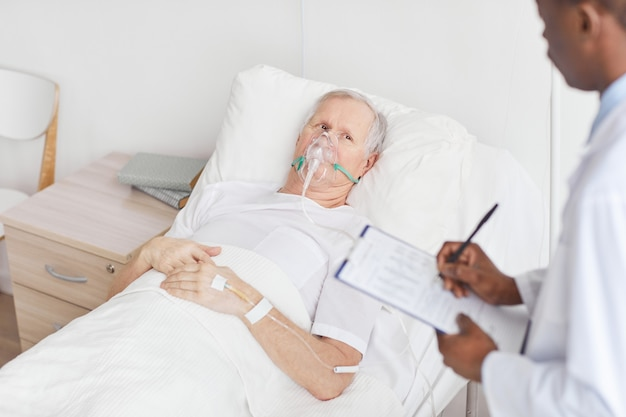 Высокий угол портрета пожилого человека, лежащего на больничной койке с кислородной маской и смотрящего на афро-американского врача, копией пространства