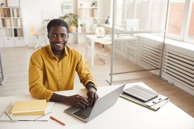 노트북을 사용하고 최소한의 사무실 인테리어에서 작업을 즐기면서 카메라를보고 웃는 아프리카 계 미국인 남자의 높은 각도 초상화, 복사 공간