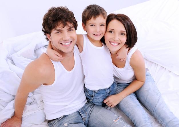 Высокий угол портрет счастливых родителей с маленьким ребенком, сидящим на кровати