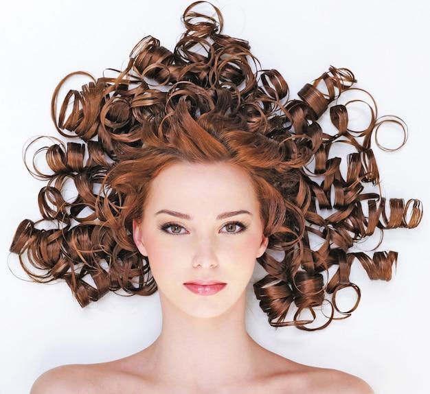 아름다움 곱슬 머리와 예쁜 젊은 여자의 높은 각도 초상화-바닥에 거짓말