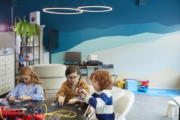 Портрет под высоким углом трех симпатичных детей, строящих роботов во время инженерных занятий в школе развития, копировальное пространство