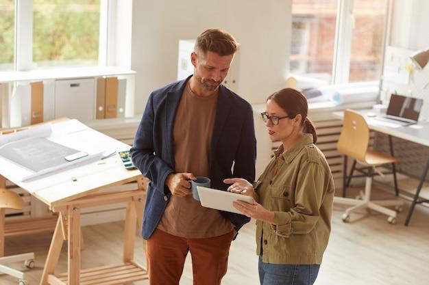 Портрет под высоким углом двух современных офисных работников, использующих цифровой планшет, стоя в офисе, освещенном солнечным светом,