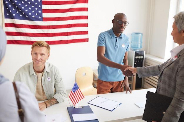 選挙日に有権者を登録している間、人々と握手している2人の投票所労働者の高角度の肖像画、コピースペース