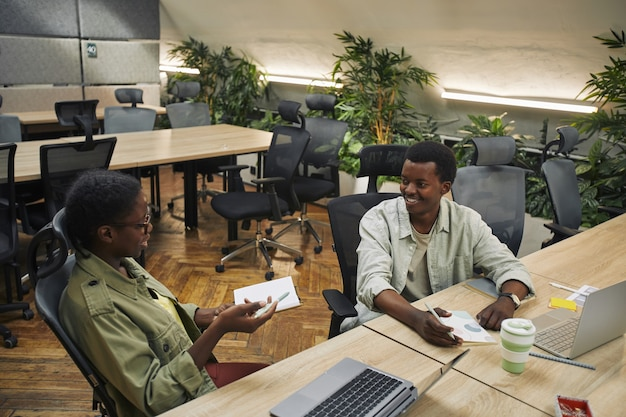 Высокий угол портрета двух молодых афро-американских людей, обсуждающих проект и улыбающихся во время работы в современном офисном интерьере, копией пространства